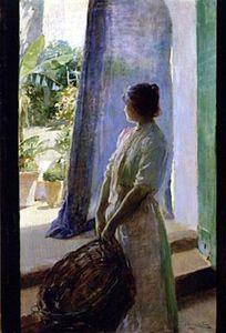 Mujer asomada a la puerta del jardín